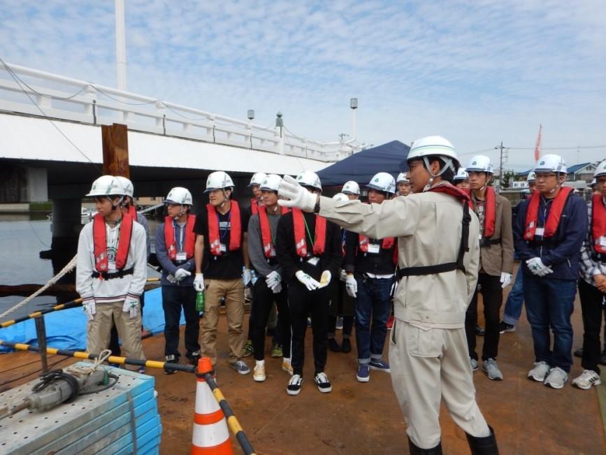 作業用台船の上で水中施工の説明を聞く